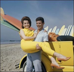 In this 1963 file photo, singer Frankie Avalon and actress Annette Funicello are seen on Malibu Beach during filming of 'Beauty Party' in California in 1963. Former 'Mouseketeer' Funicello died Monday.