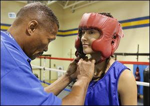 Coach Darrie Riley fastened the head gear of Monica Van Pelt in August, 2011. The then-15-year-old boxer represented Toledo's Police Athletic League,