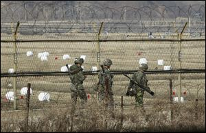 South Korean army soldiers patrol along a barbed-wire fence near the border village of Panmunjom in Paju, South Korea, today.