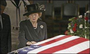 Former British Prime Minister Margaret Thatcher pauses at the casket of former U.S. President Ronald Reagan as he lies in state in the Capitol Rotunda on June 9, 2004.