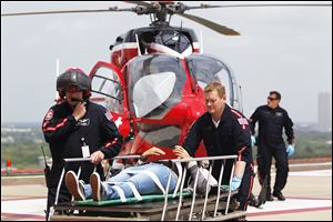 Life Flight personnel rush a victim today wounded in a stabbing attack on the Lone Star community college system's Cypress, Texas campus into Memorial Hermann Hospital in Houston.