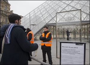 A visitor stands in front of to entrance in Louvre museum Paris, France, today. Paris' famed Louvre museum has been closed after workers walked off the job to protest what they say is the increasing problem of pickpockets.