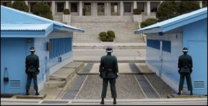 A North Korean soldier, center top, looks at the southern side as South Korean soldiers stand guard at the border village of Panmunjom, which has separated the two Koreas since the Korean War, in Paju, north of Seoul, South Korea, today.