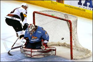 Walleye goalkeeper Kent Simpson blocks down a shot by Cincinnati's Garrett Wilson in the first period.