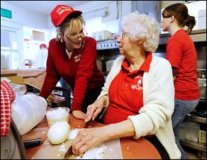 Cindy Leffler, left, talks with her  mother, Maxine Haas, as she chops onions at Pee Wee's Dari Snak in Stony Ridge. Ms Haas' father started the family business, which is marking its 50th anniversary.