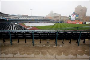 Seats are reflected in standing water and a tarp covers the playing surface Wednesday at Fifth Third Field. Weather permitting, the Mud Hens will play their home opener today against Louisville.