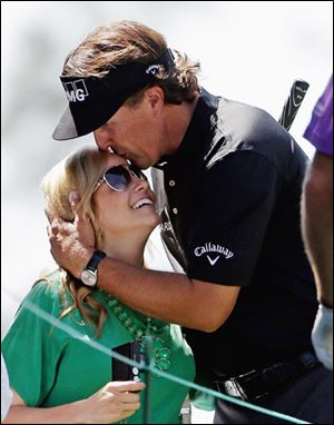 Phil Mickelson kisses his wife Amy on Wednesday during the par-3 tournament.