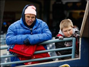 Pauline Lanctot of Carsonville, Mich., and Ian Malkoski, 11, of Toledo, wait for the start of the Toledo Mud Hens