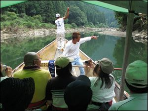 An oarsman pilots an excursion boat down the Hozu River, just outside Kyoto, Japan, as a guide points out sights to his passengers. The two-hour ride offers the chance to spot wildlife while threading rocks and rapids, and is an especially appealing outing for a trip with children.