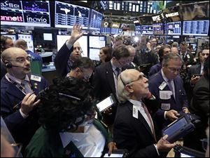 Traders gather at a post on the floor of the New York Stock Exchange today. Stock indexes are little changed in early trading on Wall Street after three days of gains.