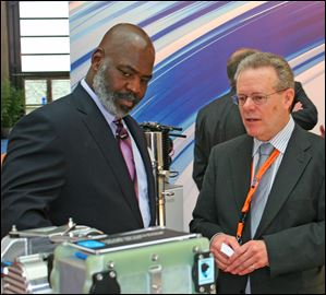 In between meetings at Hannover Messe, in Germany, Mayor Mike Bell stops to talk with Dana excutives. Brian Cheadle, director of global business development, shows the mayor fuel cell technology, including its newly announced Metallic Bipolar Plates.