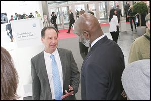 Paul Zito, vice president for international development for the Regional Growth Partnership, talks strategy with Mayor Mike Bell near the Volkswagen display.