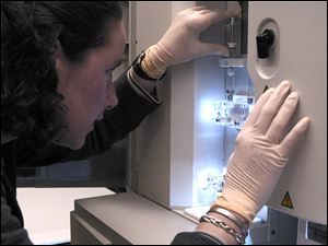 In this image provided by the National Human Genome Research Institute, a NHGRI researcher monitors a DNA sequencing machine at the NIH in Bethesda, Md.