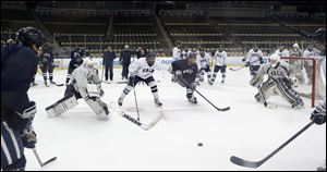 Yale players work on a drill between goaltenders Jeff Malcolm, left, and Nick Maricic, right, during NCAA college hockey practice Friday at the Frozen Four in Pittsburgh. Yale takes on Quinnipiac on the championship game today.