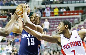 The Pistons' Brandon Knight (7) reaches in on the Bobcats' Kemba Walker (15) during the first half of Friday's game at The Palace of Auburn Hills.