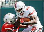 Grey running back Warren Ball  breaks a tackle by Scarlet linebacker David Perkins on Saturday.