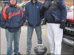 Chris Wurn, Matt Luchi, and Ron Simpson shiver in the cold as they grill brats, chicken, and steak to stay warm. A few other tailgaters in the parking lot across from the main gate, took a break and sat in their cars,
