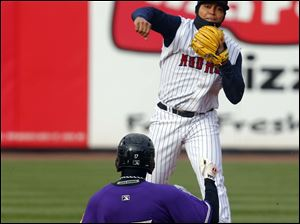 Toledo Mud Hens player Gustavo Nunez turns the double play as he forces out Louisville Bats player Kristopher Negron (17) during the first inning.