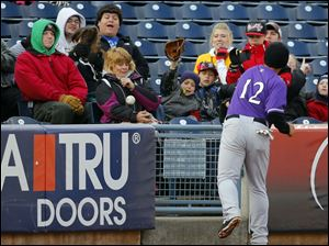 Louisville Bats third baseman Henry Rodriguez (12) can't grab a Toledo Mud Hens foul ball as it almost hits a fan during the first inning.