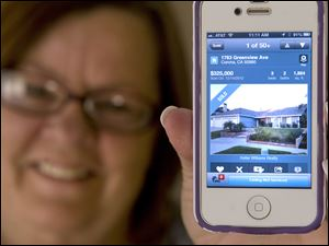 Donna Chapman opens the Redfin app on her iPhone and shows off the sold sign banner attached to a photo of her new home in Corona, California.