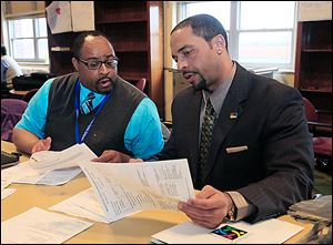 Romules Durant, right, reviews a report with David Manley, special education coordinator-supervisor for Rogers High School, during a recent meeting at the Toledo Technology Academy in West Toledo.