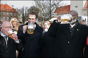 Toledo Mayor Mike Bell, right, and Patrick de La Lanne, center, mayor of Delmenhorst, Germany, celebrate a yearly spring festival with a mug of beer.