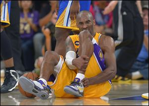 Los Angeles Lakers guard Kobe Bryant grimaces after being injured during the second half Friday against the Golden State Warriors in Los Angeles. The Lakers won 118-116.