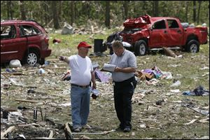 William White, left, speaks to his insurance agent Rick Anderson, from USAA, right, to asses the damage to his home and property that was destroyed by the tornado. White's truck, behind, was blown into their backyard.