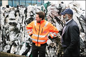 Sebastian Koch, left, shows Mayor Mike Bell bales of plastics that will be recycled at the city-owned waste management facility in Delmenhorst, Germany.
