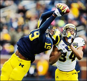 Michigan tight end Devin Funchess makes a catch against safety Jeremy Clark to help set up a score.