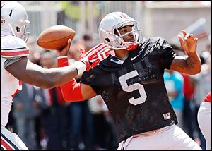 Braxton Miller passes while under pressure from Adolphus Washington, who had four sacks.