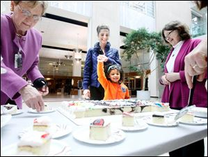 Frankie Ramsdell-Washington, center, 3, and her mother Morgan Ramsdell, center back, look forward to a piece of cake being served by Margaret Danziger, Deputy Director of the Library, left, and Louise Ehrick, President, Friends of the Library Board of Trustees, right.