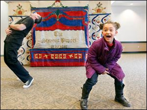Puppeteer Greg Genna, left, and audience member Annika Oestrike, 6, of Toledo laugh after a pre-performance dance.