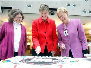 Sharon Meinerding, center, trustee with Friends of the Library Board of Trustees, cuts the cake while being flanked by Louise Ehrick, president, Friends of the Library Board of Trustees, left, and Margaret Danziger, Deputy Director of the Library.