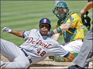 The Tigers' Torii Hunter slides in safely to score past the A's Derek Norris in the first inning. Hunter scored on a single by Victor Martinez to open up the floodgates in a 10-1 Tigers victory.