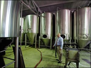 Neal Kovacik, general manager at the Oliver House, is dwarfed by fermentation tanks.