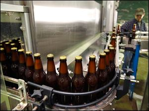 Jeff Kerekes monitors bottled beer as it moves from the bottling machine to the pasteurizer.