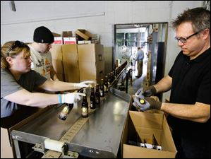 Shannon Mohr, brewery manager, Chad Bukowski, bottler, and Matt Snyder, Middle Grounds market manager, pack bottled beer as it comes off the production line.
