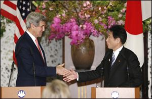 U.S. Secretary of State John Kerry shakes hands with Japanese Foreign Minister Fumio Kishida in Tokyo. Japan said Sunday that it is open to talks with North Korea if Pyongyang honors previous agreements.