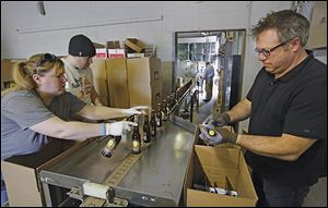 Shannon Mohr, brewery manager, Chad Bukowski, bottler, and Matt Snyder, Middle Grounds market manager, pack bottled beer as it comes off the production line at the Maumee Bay Brewing Co.
