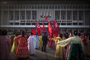 A man, center, supervises a dancing group  during a mass folk dance in front of the Pyongyang Indoor Stadium in Pyongyang, North Korea, today.