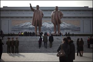 People visit statues of the late North Korean leaders Kim Il Sung, left, and Kim