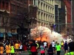 In this image from video by WBZ-TV, spectators and runners flee from what was described as twin explosions that shook the finish line of the Boston Marathon.
