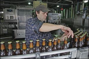 Jeff Kerekes moves beer bottles to the labeling track at the Maumee Bay Brewing Co.