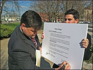 Joe McNamara, left, with campaign aide Andrew Grun-wald, signs an ethics pledge that calls on officials who supervise employees to ban them from campaigning for their bosses during normal business hours.