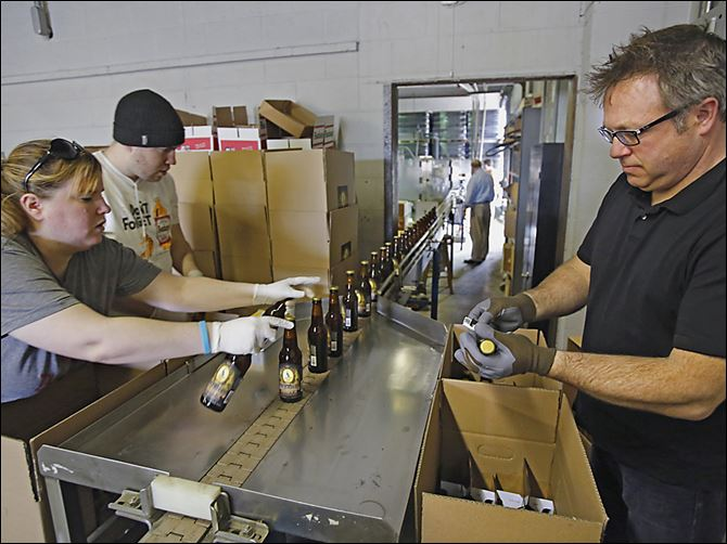 Maumee brew bottles Shannon Mohr, brewery manager, Chad Bukowski, bottler, and Matt Snyder, Middle Grounds market manager, pack bottled beer as it comes off the production line at the Maumee Bay Brewing Co.