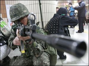 A South Korean army soldier aims his machine gun during an anti-terrorism drill against possible terrorists' attacks at a subway station in Seoul, South Korea, Monday.