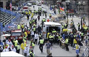 Medical workers aid injured people at the finish line of the 2013 Boston Marathon following an explosion in Boston, Monday afternoon.