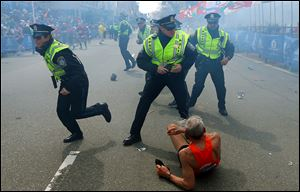 Bill Iffrig, 78, lies on the ground as police officers react to a second explosion at the finish line of the Boston Marathon in Boston, Monday. Iffrig, of Lake Stevens, Wash., was running his third Boston Marathon and near the finish line when he was knocked down by one of two bomb blasts.