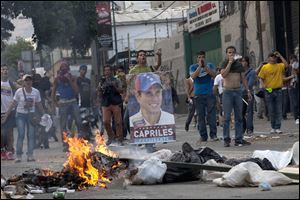 Demonstrators, one holding a poster of opposition presidential candidate Henrique Capriles, confront riot police from behind a burning barricade in the Altamira neighborhood in Caracas, Venezuela, Monday.